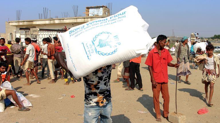 Displaced Yemenis receive humanitarian aid, donated by the World Food Programme (WFP) in the northern province of Hajjah in December 2019
