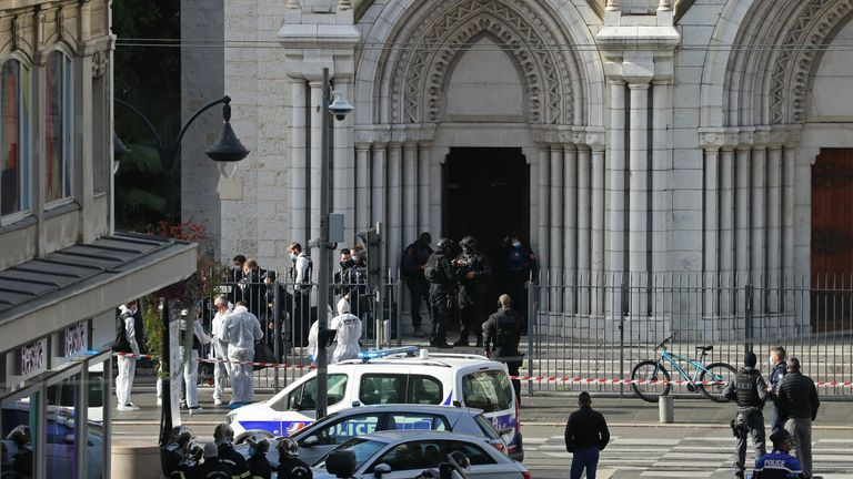 French members of the elite tactical police unit RAID enter to search the Basilica of Notre-Dame de Nice as forensics officers wait outside after a knife attack in Nice on October 29, 2020. - A man wielding a knife outside a church in the southern French city of Nice slit the throat of one person, leaving another dead and injured several others in an attack on Thursday morning, officials said. The suspected assailant was detained shortly afterwards, a police source said, while interior minister