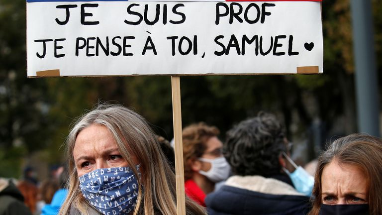 A woman holds a banner as she attends a tribute to Samuel Paty, the French teacher who was beheaded on the streets of the Paris suburb of Conflans St Honorine, at the Place de la Republique, in Lille, France, October 18, 2020. REUTERS/Pascal Rossignol