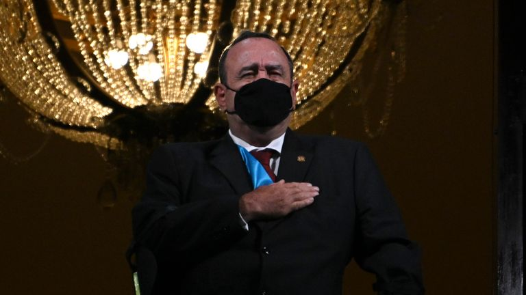 Alejandro Giammattei wearing a face mask, sings the national anthem during independence celebrations earlier this month