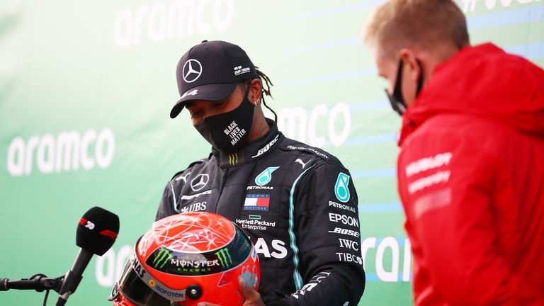 NUERBURG, GERMANY - OCTOBER 11: Race winner Lewis Hamilton of Great Britain and Mercedes GP is presented with a helmet of Michael Schumacher by his son Mick Schumacher of Germany and Alfa Romeo Racing for matching his record of 91 race wins during the F1 Eifel Grand Prix at Nuerburgring on October 11, 2020 in Nuerburg, Germany. (Photo by Bryn Lennon/Getty Images)