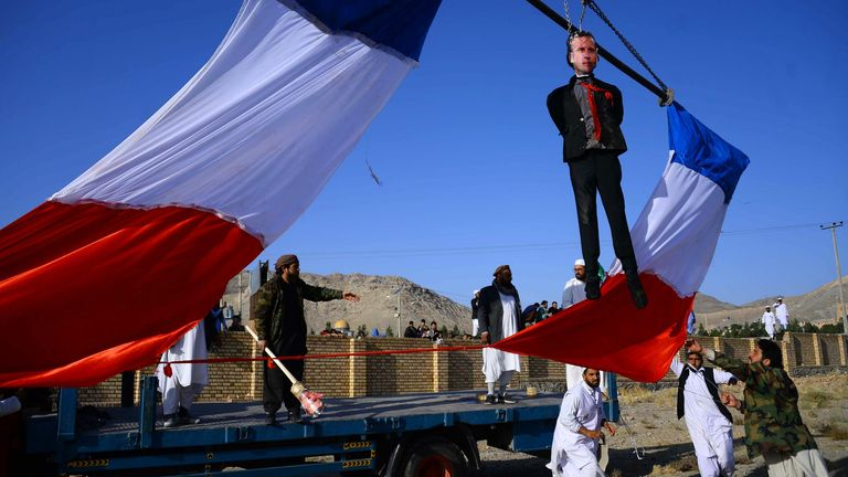 Demonstrators hang an effigy of Emmanuel Macron near Herat in Afghanistan