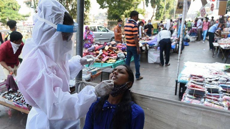 A health worker collects a swab sample from a woman to test for the Covid-19 coronavirus at a market place in Ahmedabad on October 29, 2020. - India on October 29 passed eight million coronavirus cases, with the world's second-worst-hit country bracing for a possible second wave ahead of winter and a series of religious festivals. (Photo by SAM PANTHAKY / AFP) (Photo by SAM PANTHAKY/AFP via Getty Images)