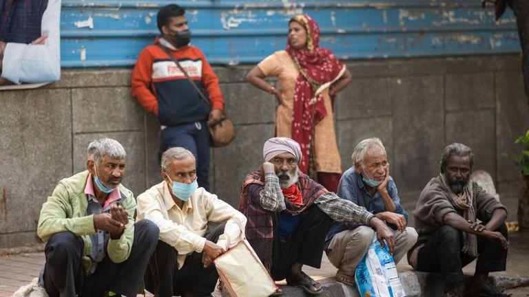 People wait at a street outside a temple to get free food in New Delhi on October 29, 2020. - India on October 29 passed eight million coronavirus cases, with the world's second-worst-hit country bracing for a possible second wave ahead of winter and a series of religious festivals. (Photo by Jewel SAMAD / AFP) (Photo by JEWEL SAMAD/AFP via Getty Images)