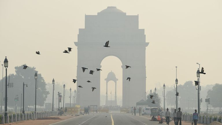 TOPSHOT - Indian pedestrians walk near the India Gate monument amid heavy smog in New Delhi on October 28, 2016. - India's capital, with 18 million residents, has the world's most polluted air, worsening in winter as temperatures drop and farmers burn off fields after the summer harvest. (Photo by Dominique Faget / AFP) (Photo by DOMINIQUE FAGET/AFP via Getty Images)