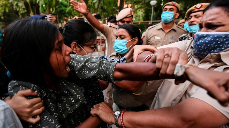 A female student clashes with police in a protest in New Delhi