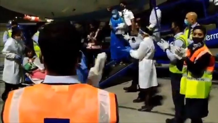 Airport crew applaud as the mother and newborn are safely taken off the flight