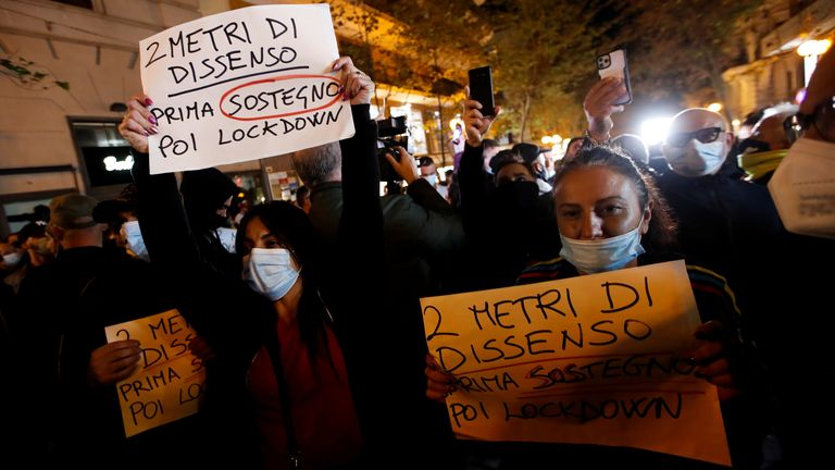 "The spread of coronavirus disease (COVID-19) in Naples Shop owners hold signs during a protest against restrictive measures in Naples as new coronavirus disease (COVID-19) cases soar to new records in Naples, Italy, October 25, 2020. The sign reads: ""2 meter of protest, first welfare then lockdown"" REUTERS/Ciro De Luca"