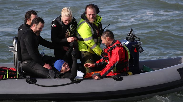 Former paratrooper John Bream (centre, wearing blue hat) is picked up from the water