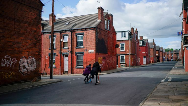 Two children scoot down an empty street in Leeds during the coronavirus pandemic