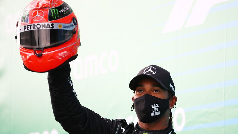 NUERBURG, GERMANY - OCTOBER 11: Race winner Lewis Hamilton of Great Britain and Mercedes GP celebrates after being presented with a helmet of Michael Schumacher for matching his record of 91 race wins during the F1 Eifel Grand Prix at Nuerburgring on October 11, 2020 in Nuerburg, Germany. (Photo by Bryn Lennon/Getty Images)