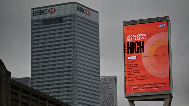 "A sign displaying the Local Covid Alert Level as ""HIGH"" is pictured near Canary Wharf in east London, on October 17, 2020, as Londoners face more stringent novel coronavirus COVID-19 restrictions as the number of cases rises. - The government has announced that London has moved into tier two, the high alert level, of a three tier system of restrictions. (Photo by JUSTIN TALLIS / AFP) (Photo by JUSTIN TALLIS/AFP via Getty Images)"