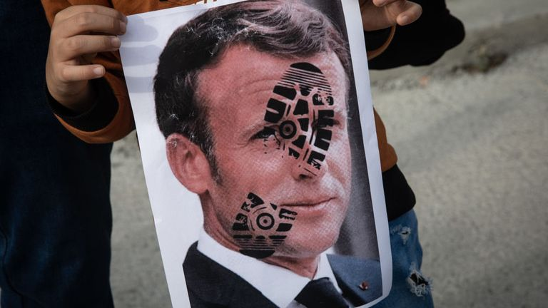 A boy  in Istanbul holds a poster a footprint on the French president's face