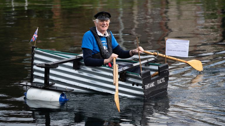 Michael Stanley, who is also known as 'Major Mick', 80, rows along the Chichester canal, West Sussex, in his home-made rowing boat, named the Tintanic. Major Mick, 80, is rowing along the Chichester canal for a 100-mile charity challenge, rowing 3 miles at a time, to raise money for St Wilfrid's Hospice in Bosham.