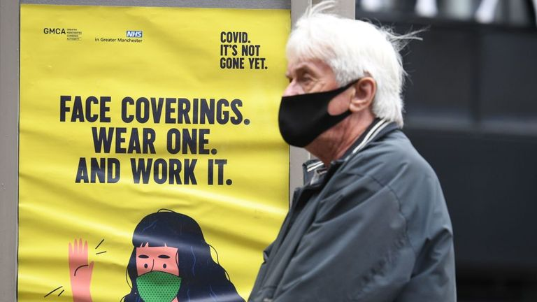 A man seen wearing a face mask as he walks through Manchester during the pandemic