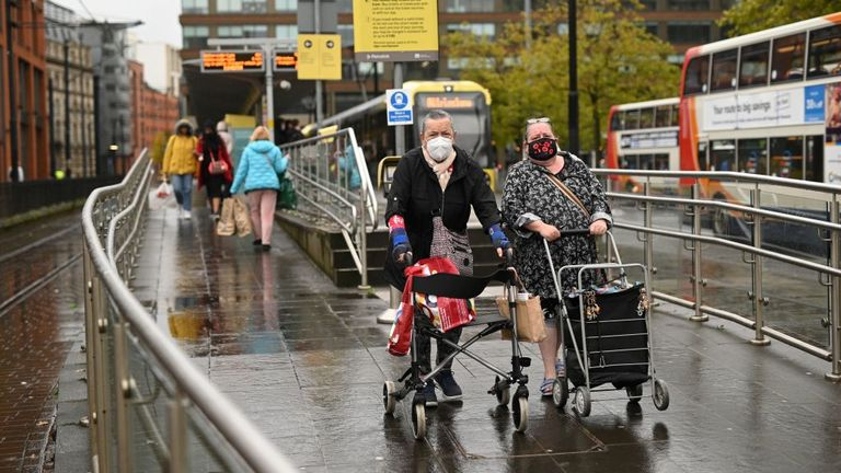 Mask-wearing pedestrians are seen in Manchester ahead of possible tighter restrictions
