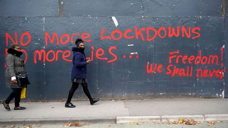 MANCHESTER, ENGLAND - OCTOBER 19: People walk past anti-lockdown graffiti on October 19, 2020 in Manchester, England. Greater Manchester's leaders including Mayor Andy Burnham will want better financial arrangements for workers affected before they agree for the region to be moved into Tier 3 Covid-19 lockdown. (Photo by Christopher Furlong/Getty Images)