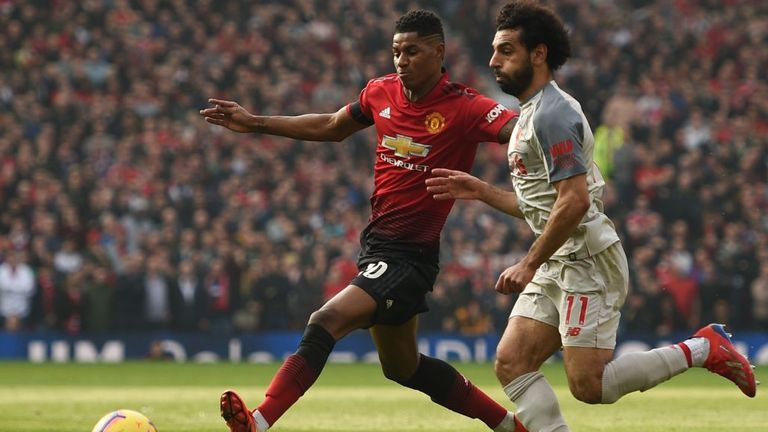 Manchester United's Marcus Rashford, left, and Liverpool's Mo Salah are seen competing for the ball