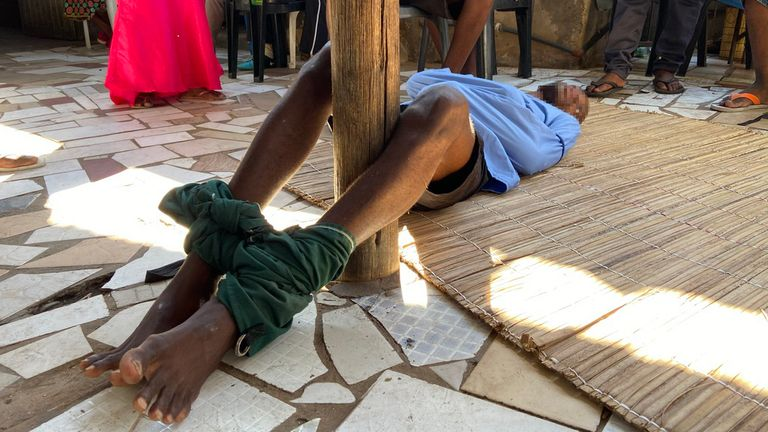 """A man with a mental health condition lies on the floor with his legs tied around a wooden pole and his arms in a straitjacket at a church outside Maputo, Mozambique. The church pastor provides spiritual guidance and uses the word of God to """"fight evil spirits."""""""