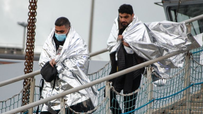 Two men walk returning to Calais after being picked up with 15 others  by a rescue boat