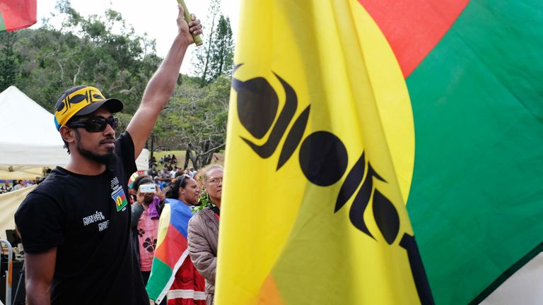 An independence supporter stands near a flag of the Socialist Kanak National Liberation Front