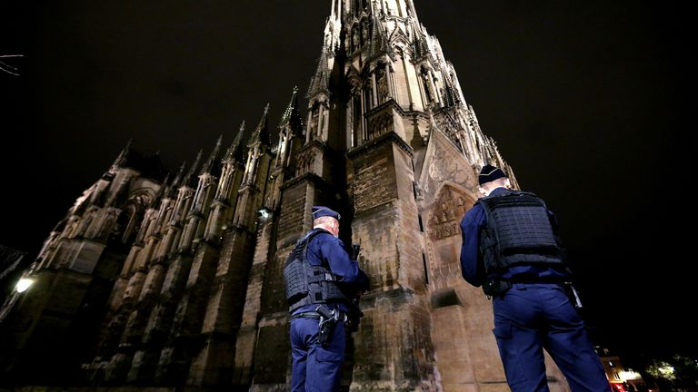 "Police stand guard outside the the Notre-Dame de Reims cathedral in Reims, eastern France, on October 30, 2020, ahead of a ""mass for France"" in homage to the three victims of a knife attack at a church in Nice the previous day."