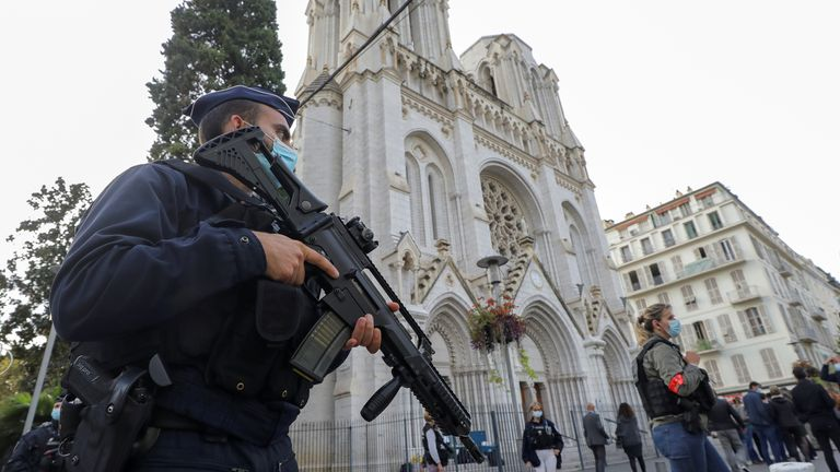 An armed police officer stands guard near Notre Dame church where the attack took place