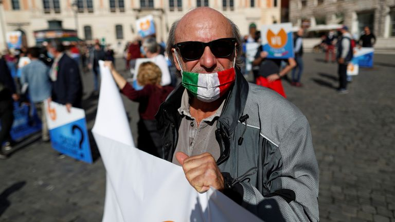Demonstrators protest against restrictive measures put in place to fight COVID-19, in Rome A demonstrator wears a protective mask with the Italian flag during a protest against restrictive measures put in place to fight the coronavirus disease (COVID-19) infections in Rome, Italy, October 25, 2020. REUTERS/Yara Nardi