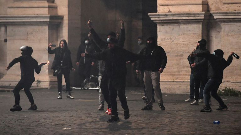 People clash with police as they protest against the government restriction measures to curb the spread of Covid-19 in Rome, on October 27, 2020. - Thousands of Italian protesters angry over new restrictions announced to control the spread of coronavirus clashed with police in cities on October 26, 2020, following weekend demonstrations that saw violence in Italy, as European governments toughened their responses to the contagion. (Photo by Tiziana FABI / AFP) (Photo by TIZIANA FABI/AFP