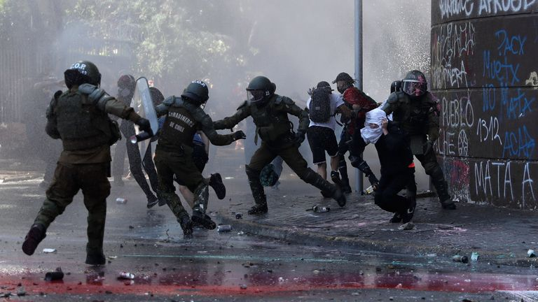 Riot police clash with demonstrators on the streets of Santiago