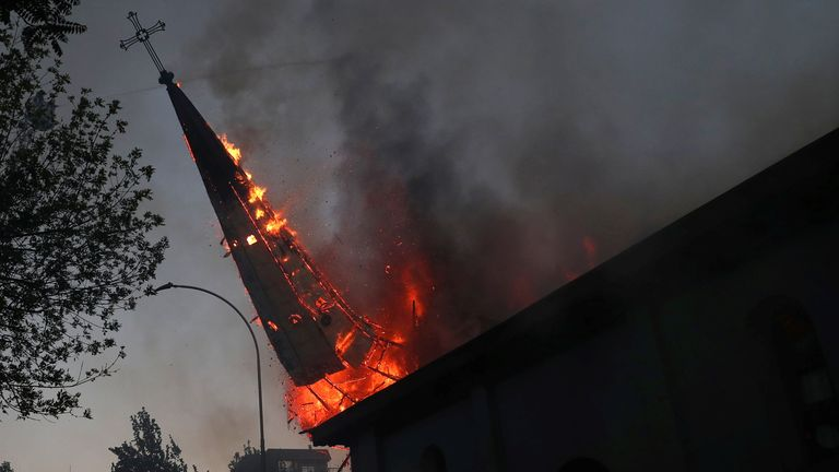 A burning church spire falls to the ground after being set on fire in the Chilean capital