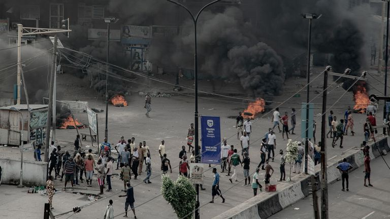 People are seen near burning tires on the street, in Lagos (UnEarthical/via Reuters)