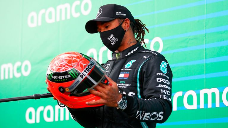Winner Mercedes' British driver Lewis Hamilton holds the red helmet of former German Formula one champion Michael Schumacher that was offered to him by Mick Schumacher