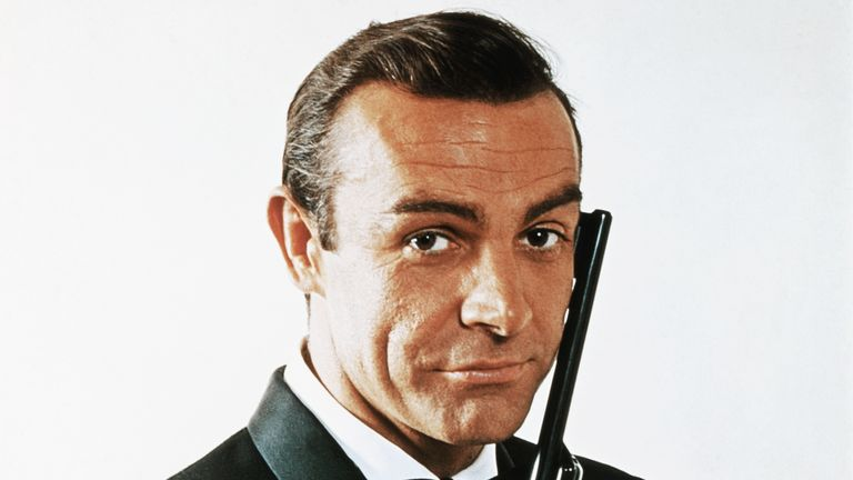 (Original Caption) Waist-up portrait of Sean Connery, as James Bond, caressing the barrel of a gun against the side of his face. Connery is wearing a tuxedo and bow tie and smiling slightly.