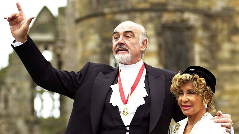 Sir Sean Connery, with wife Micheline (R), pose for photographers after he was formally knighted by ..