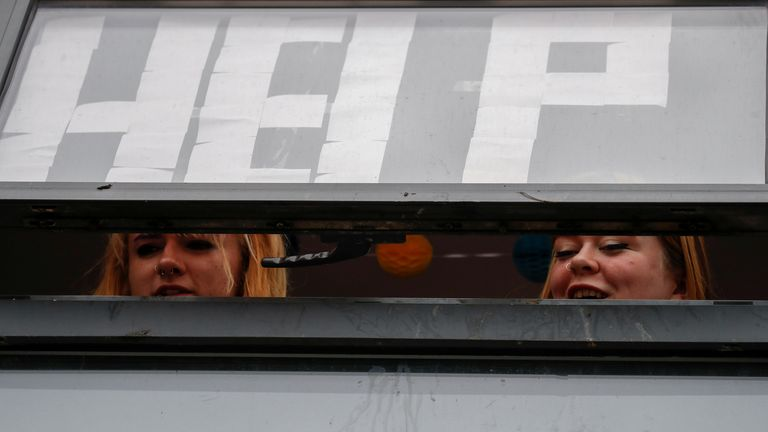 Students with a sign displayed on the window of their accommodation in Manchester