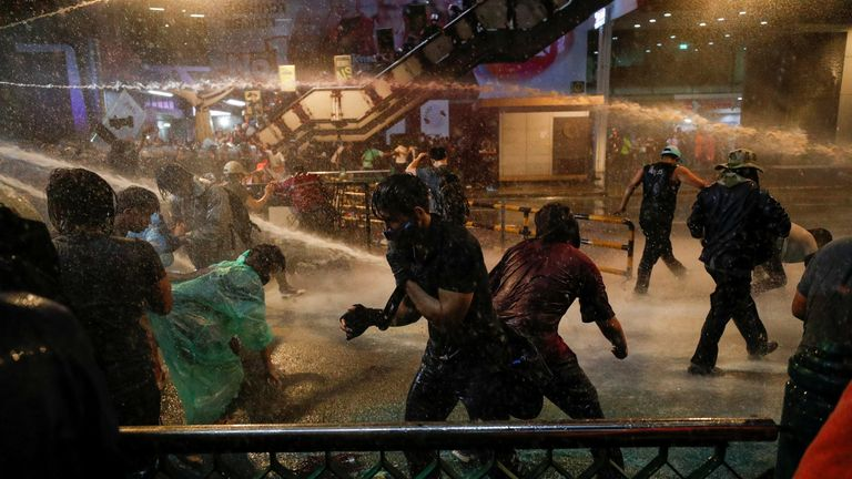 People are hit with water from water cannons during an anti-government protest, in Bangkok