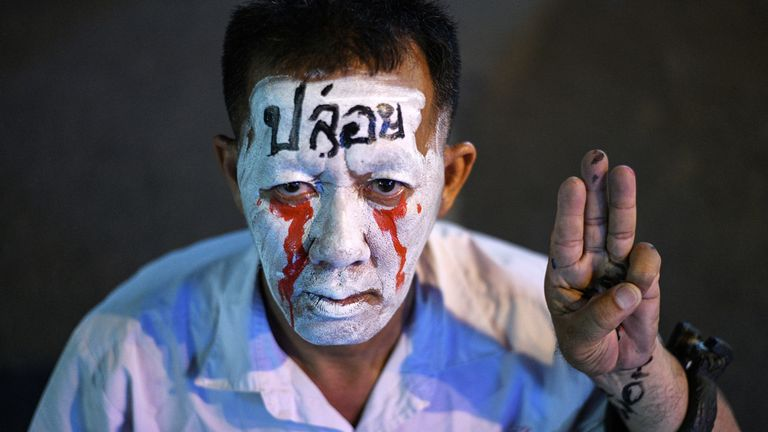 A man shows the three-finger salute the protestors have been using during their demonstrations