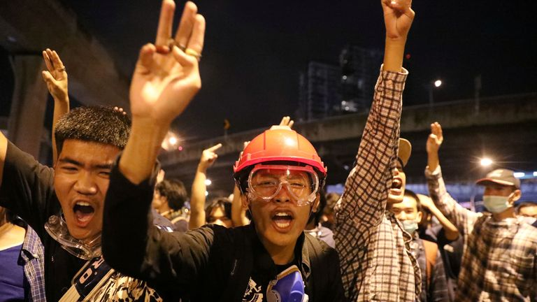 Pro-democracy protesters show the three-finger salute