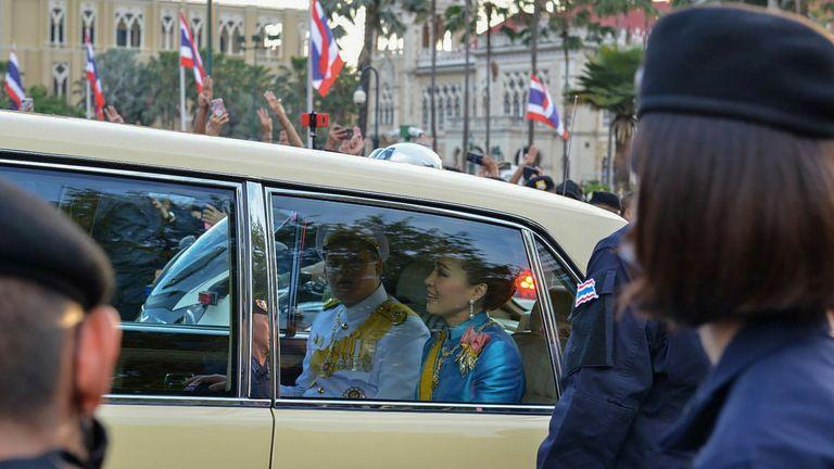 Queen Suthida and Prince Dipangkorn Rasmijoti, of the Thai royal family, react as the royal motorcade passes pro-democracy protesters hold up three finger salutes. (Photo by Teera NOISAKRAN / AFP) (Photo by TEERA NOISAKRAN/AFP via Getty Images)