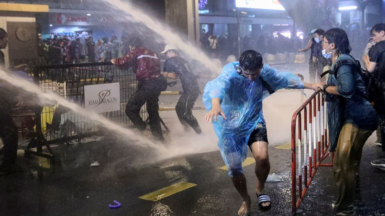 People are hit with water from water cannons during anti-government protests, in Bangkok