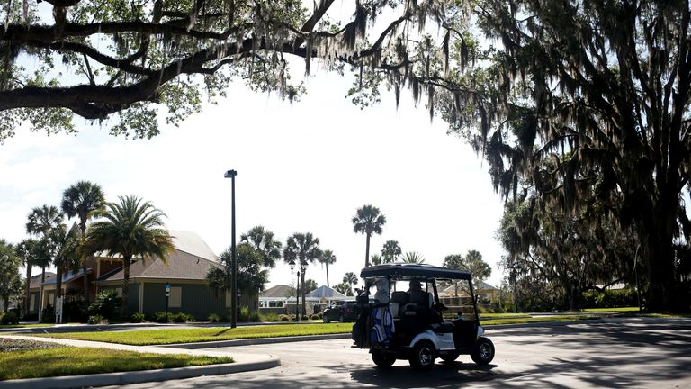 A retiree drives a golf cart amidst coronavirus-related event cancellations at Fenney Recreation Center in The Villages, Florida,