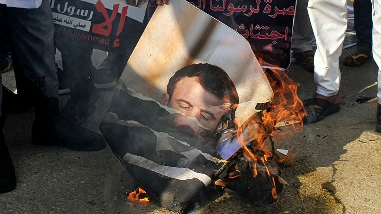 Protesters burn a portrait of French President Emmanuel Macron in Tripoli