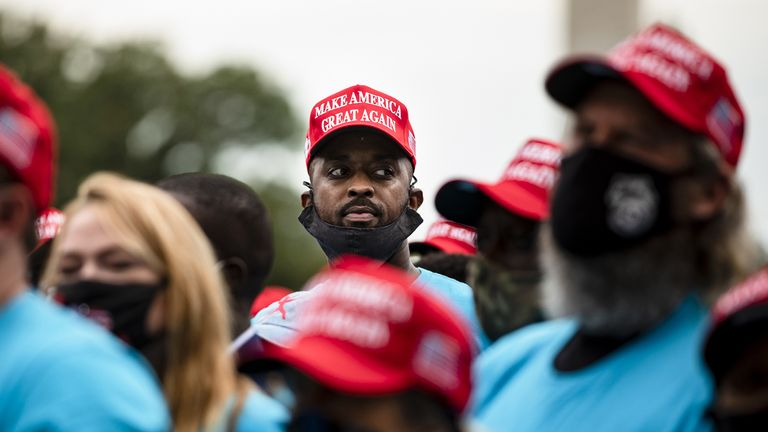 A man wearing a Make America Great Again and a t-shirt with the 'Blexit' campaign logo watches Donald Trump