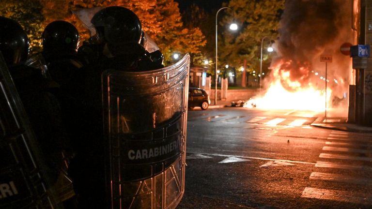 Police officers stand guard as protesters set fire to public property during an anti government demonstration