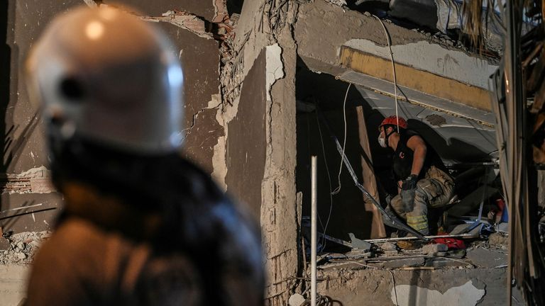 A rescuer searches for survivors among the rubble of a collapsed building after a powerful earthquake struck Turkey's western coast and parts of Greece, in Izmir, on October 30, 2020.