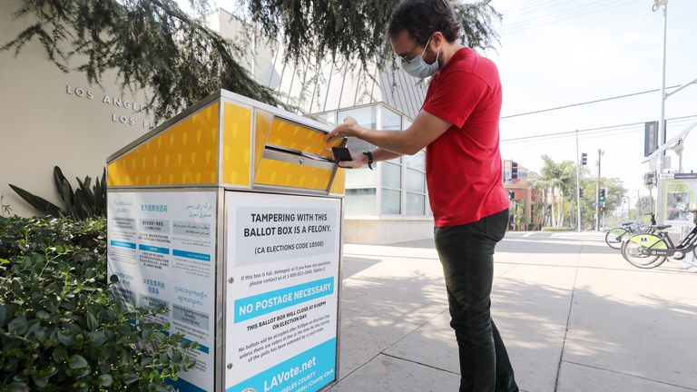 A voter places his ballot in a drop box in Los Angeles