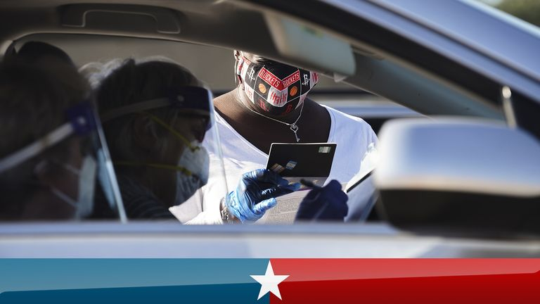HOUSTON, TX - OCTOBER 07: An election worker accepts mail in ballot from voters with face shields at drive-through mail ballot drop off site at NRG Stadium on October 7, 2020 in Houston, Texas. Gov. Gregg Abbott  issued an executive order limiting each Texan county to one mail ballot drop-off site  due to the pandemic. (Photo by Go Nakamura/Getty Images)