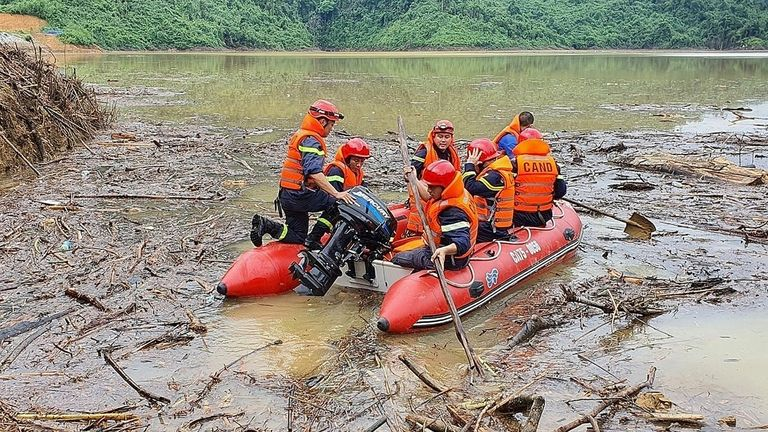 Vietnamese search and rescue personnel attempt a rescue at the Huong Dien hydroelectric project after landslides