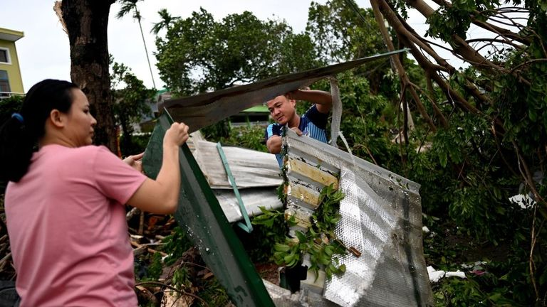 A couple clears debris outside their house